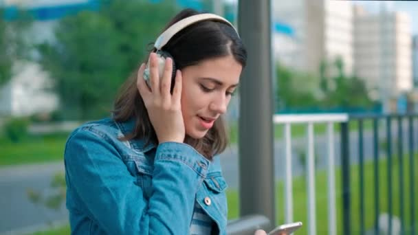 Young woman listening to music sitting on bench