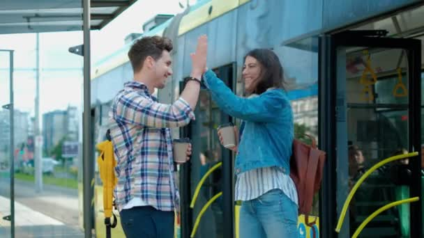Happy couple meets at the tram stop. high fives to each
