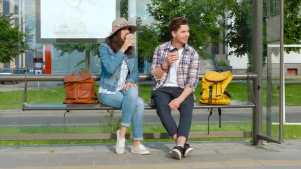 Young couple drinking coffee outdoors sitting on a bus station bench