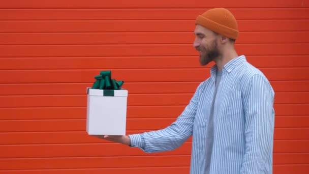 Surprised young hipster man with mustache and beard in surprise holding white box with gifts on a red background, The concept of gifts and surprises for the holiday