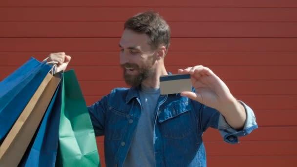 Boldog modern ember gazdaság bevásárló táskák és hitelkártya egy Toothy mosoly, nézte a kamerát. piros háttéren