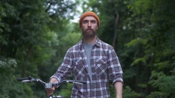 Brutální chlapík alternativců v parku s koly na opravě