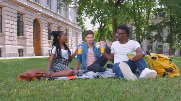 multiracial students with hamburgers relaxing in the park
