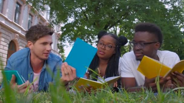Tři studenti studující čtení poznámek spolu venku sedí na trávě
