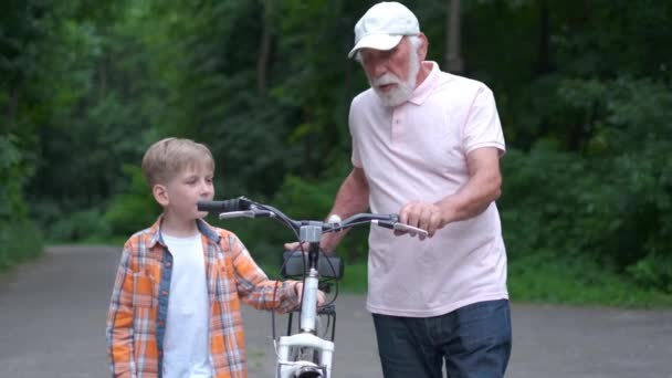 Happy grandfather teaching boy how to ride bicycle at summer park. family, generation, safety and people concept