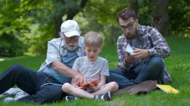 happy family of three generation - father, grandfather and blond son sitting on grass at park with books learn to read while getting ready for school.They are laugh,fun,spending good time together