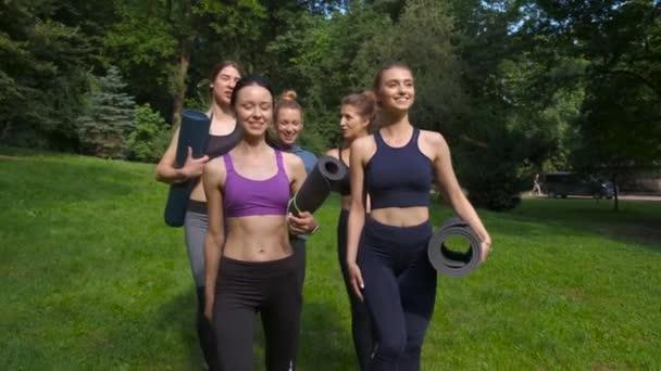 Skupina aktivních pěti usměvavé ženské, která se chystá na cvičení a v létě v parku drží rohože jóju. Životní fitness koncept v aktivním životním stylu. Dynamické pohyby. Sportovní a zdravé.