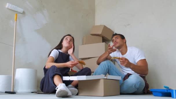 appy mladý pár jíst pizzu při opravování v novém bytě