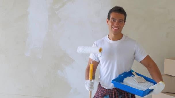 Ein lächelnder gutaussehender Mann bemalt zu Hause Wand für Wand. Reparatur, Bau und Wohnkonzept