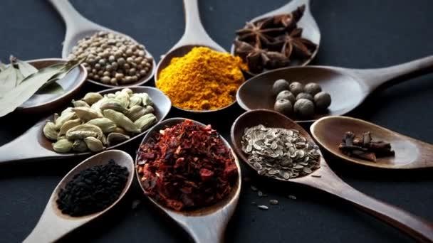 Barevné různých bylin a koření k vaření na tmavém pozadí.