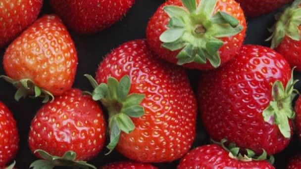 Jahody rotující na černém pozadí. Přírodní produkty jsou šetrné k životnímu prostředí.