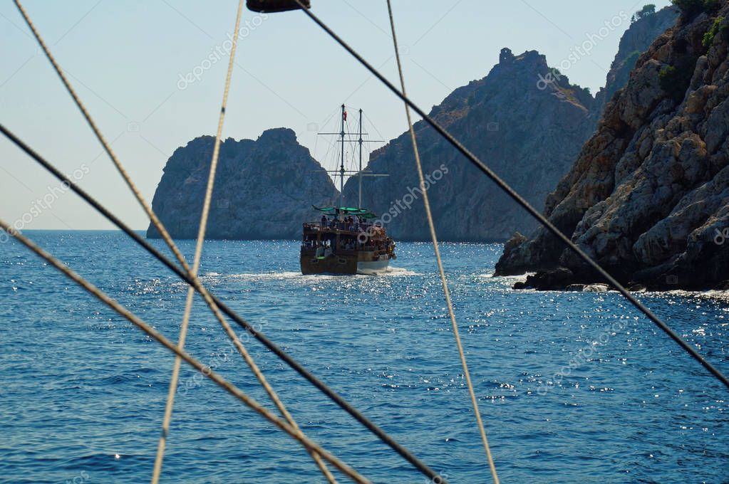 Scenic view through the cordage of a touristic sail boat in the turquoise waters of Mediterranean sea with a boat maneuvering between the rocks in Mediterranean sea beside Alanya city port in Turkey