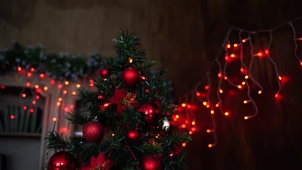 Velký vánoční stromek je zdoben krásnými červenými a oranžovými kuličkami.