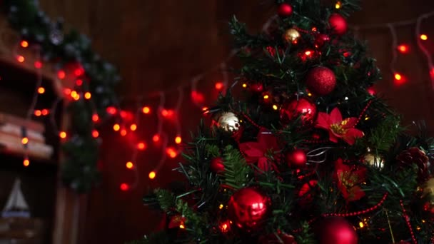 A large Christmas tree is decorated with beautiful red and orange balls.