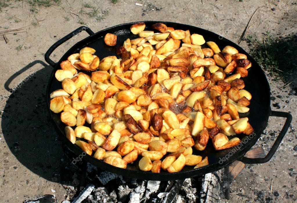 Roast potatoes on fire. Nature, firewood, fireplace on which a large frying pan, on which the oil boils, and fries potatoes are cooked. Good photos for people who promote active rest and healthy food.