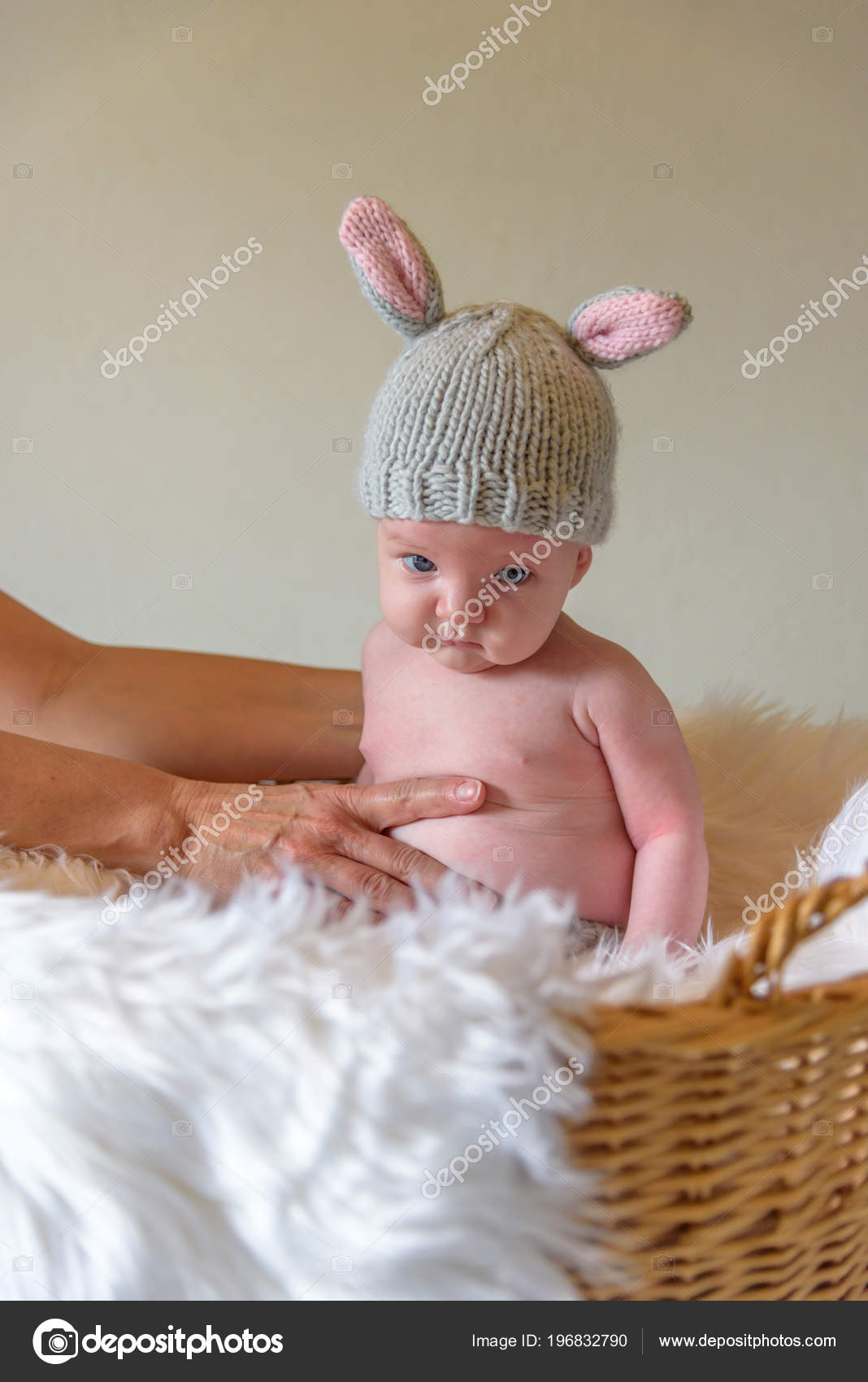 Bébé dans la maison tricot bonnet oreille de lapin assis dans le panier de  Pâques avec une drôle d expression du visage– images de stock libres de  droits 745b14e99fd