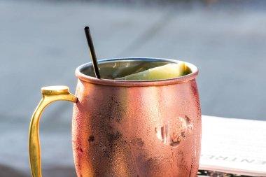 macro closeup of a moscow mule drink in copper mug outside in summer