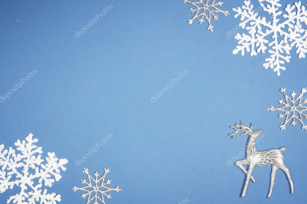 Decoration white snowflake on blue background. Christmas deer Top view