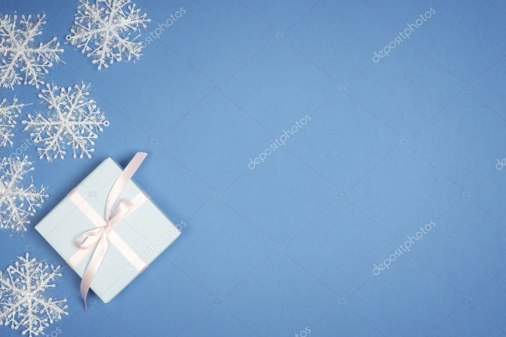 Decorative white snowflake and new year gift box on blue background. Christmas Flat lay