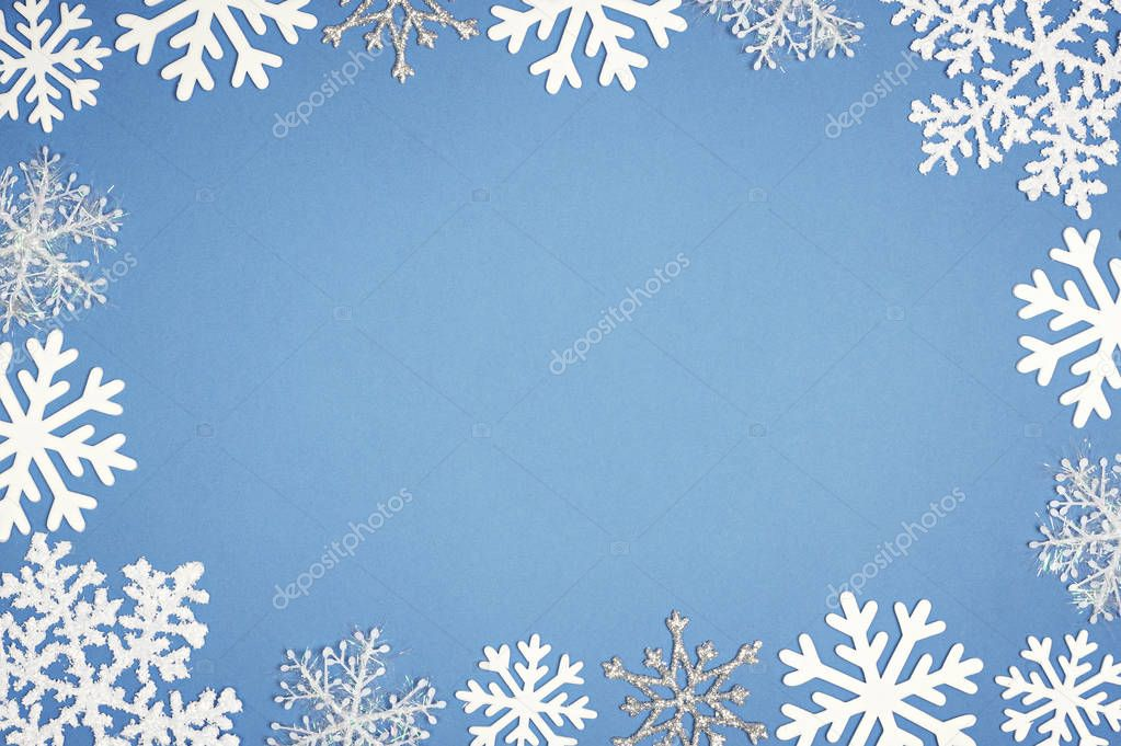 Christmas decor with snowflake on blue background. Copy space