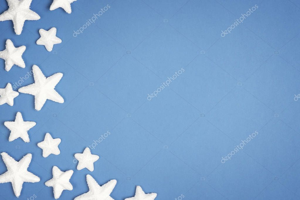 Christmas white snow stars on blue background. Top view