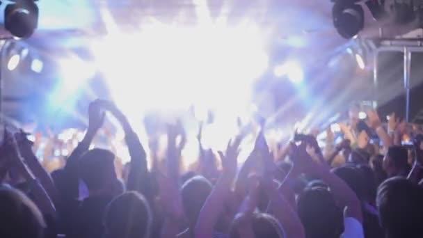 Nagy csoportja boldog ember élvezi rock koncert, taps felemelte a kezét, a színpad 1 fények