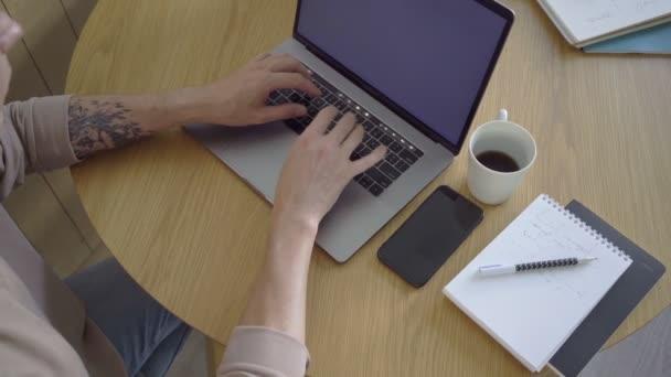Oříznout podnikatele pomocí notebooku a psát do notepadu. Oříznout muže pracující na notebooku na dřevěném stole.