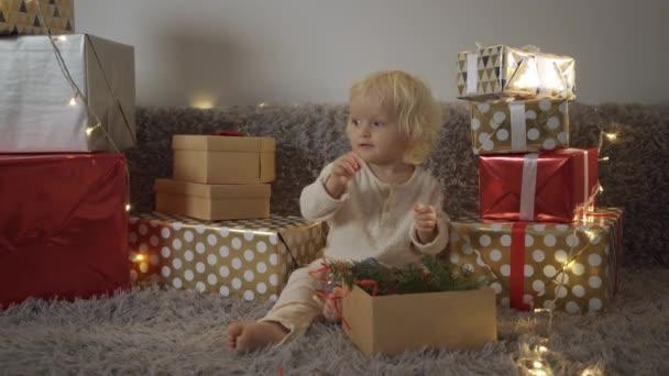 Glückliches kleines lächelndes Mädchen mit Weihnachtsgeschenkschachtel. Glückliche Geschenke für das Christkind.