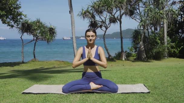 Egy nő jógázik. Gyönyörű fiatal nő csinál nyújtózkodás gyakorlat kívül.