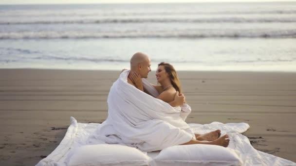 Mladý pár na pláži. Šťastný veselý pár se spolu baví. Koncept romantické dovolené, líbánky.