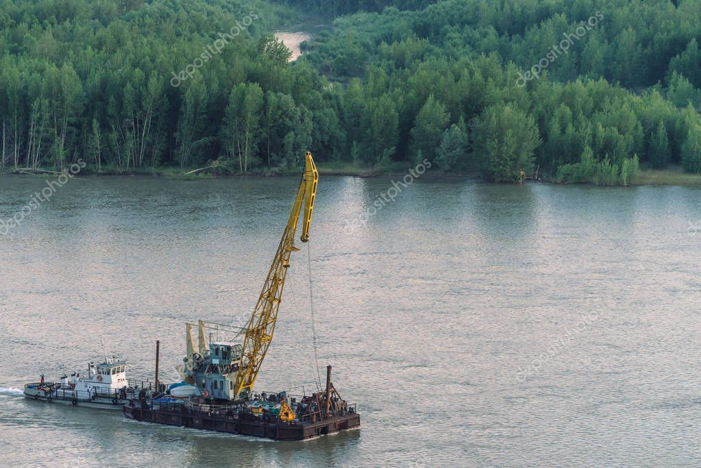 Beautiful river landscape with green shores and ship with copy space. Towboat tows barge with crane along riverbank. Dawn reflexed on calm glare water surface. Forest on background.