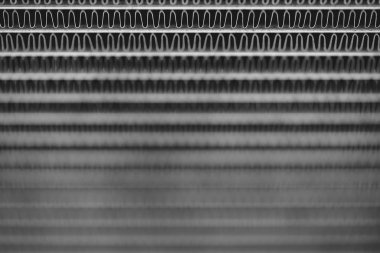 Monochrome background image of automotive radiator close up. Silver background from many duplicate lines.
