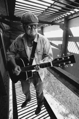 Monochrome photo of bluesman with acoustic guitar