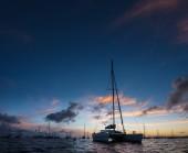 Temné noční pohled na plující lodi kotvící na otevřené moře s černá silueta ostrova