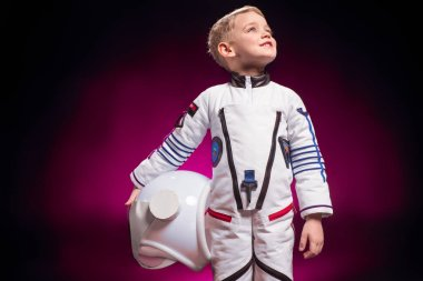 adorable boy in astronaut costume on colorful background