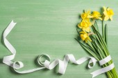 view from above of bouquet of daffodils wrapped by white ribbon on green background