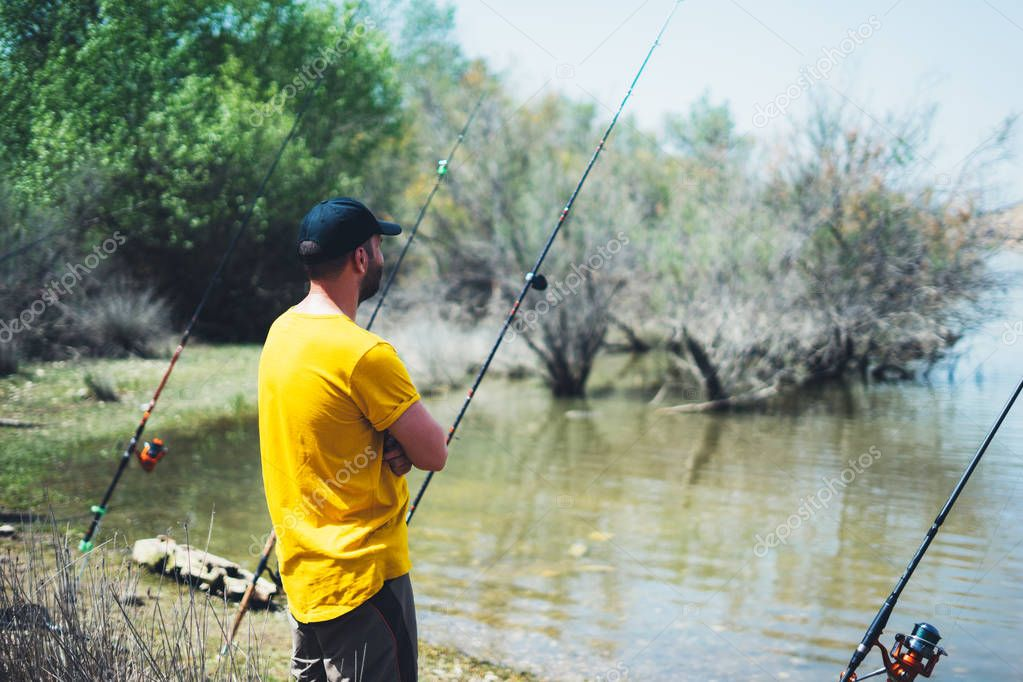 young man looking on horizont seascape and holds a fishing rod and catches fish in the nature background, hipster fisherman spends vacation on the blue ocean, active travel hobby fishing, rural outdoor sport tourism