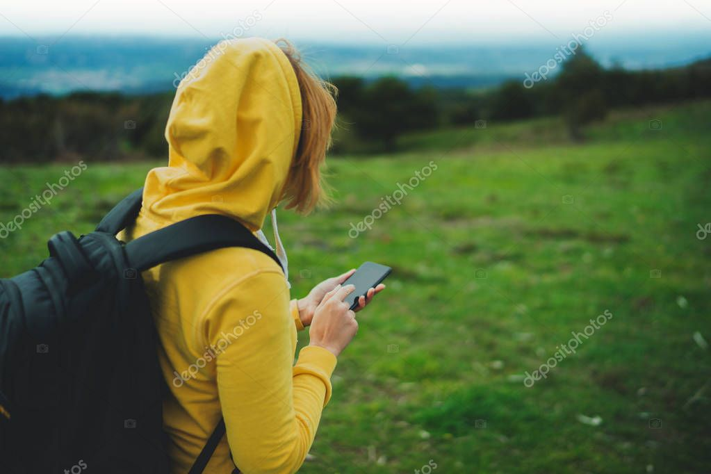 tourist girl on background green grass using mobile smart phone, person holding in female hands gadget technology, texting finger message on screen content online wifi internet lifestyle concept