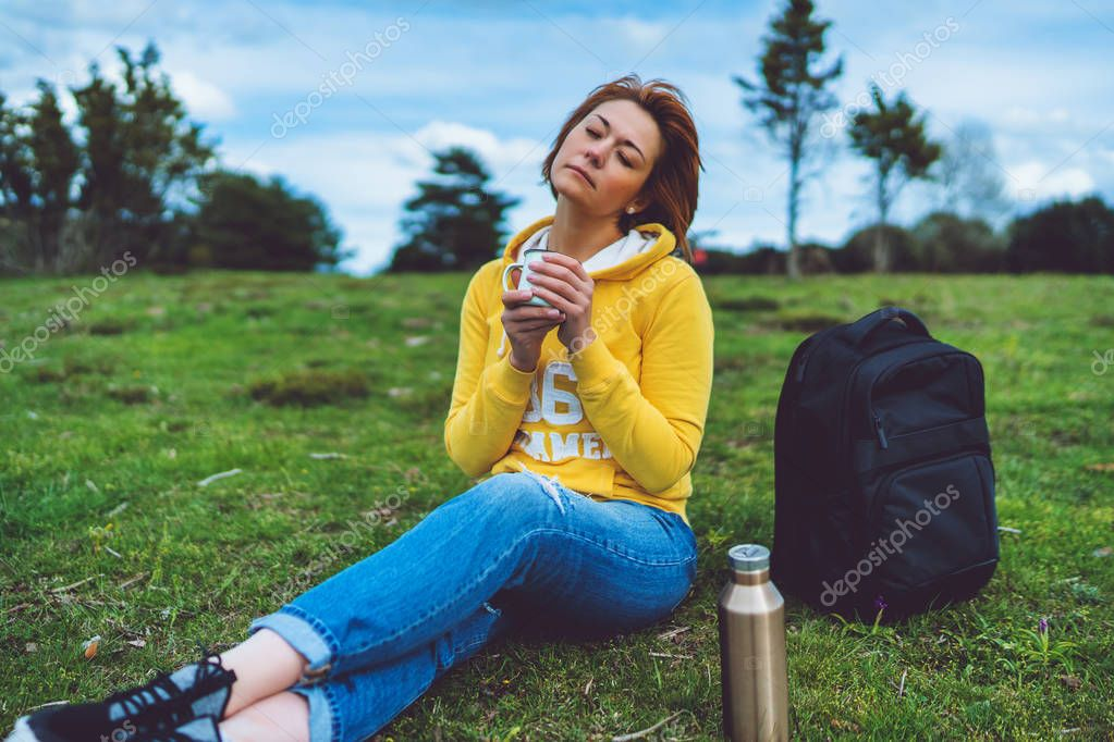 Happy girl with eyes closed holding in hands cup of hot tea on green grass in outdoors nature park, beautiful woman hipster enjoy drinking cup of coffee, lifestyle relax recreation meditation concept