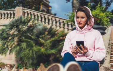 girl hold in hands mobile phone, person type message on smartphone, relax tourist travels planning trip in sun city, hipster enjoy journey in cityscape, lifestyle holiday concept