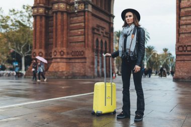 Photographer tourist with retro photo camera. Girl in hat with suitcase travels in Triumphal arch Barcelona. Holiday concept in europe street. Traveler hipster shoot architecture city