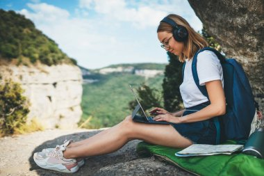 tourist girl with glasses and headphones uses digital tablet device sitting in nature outdoor, hipster woman with backpack enjoys music using headphones and laptop computer on backdrop of high mountains