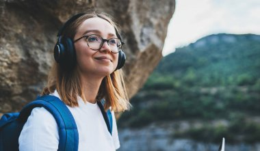 blonde female traveler with backpack on top of mountain on backdrop blue sky, active tourist woman with headphones hiking enjoys landscape and