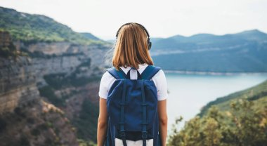view from behind young woman with blonde hair listening to music in headphones and enjoying  mountain river,  tourist with backpack looks into distance at rocky peaks of mount, summer vacation concept