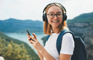 portrait smiling blonde girl with hipser glasses and backpack connection cellphone device and listens music for headphones via wireless technology to rest hiking walk on top mountains outdoors, copy space