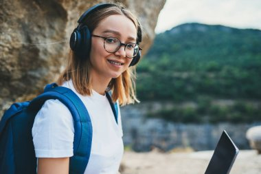 smile young girl tourist with backpack enjoying summer holidays listen music in headphones and laptop in nature, woman copywriter with glasses working on digital tablet device on backdrop landscape