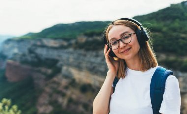 positive young traveler with long blonde hair and hipster glasses listens to favorite music in wireless headphones smiles while hike walking trip through the natural mountain landscape on summer vacation