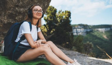 blonde girl traveler enjoys music with headphones dreaming in mountains in the fresh cleare air, young female tourist with glasses and backpack rests alone in nature and relaxes from freedom outdoor