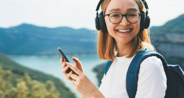 portrait smiling traveler blonde girl  with hipser glasses and backpack using  mobile phone device and listens music for headphones via Internet technology to relax hiking walk on top mountains outdoors, copy space