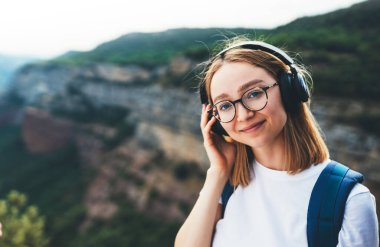 looking at camera young female traveler with blonde hair and hipster glasses listening to her favorite music in wireless headphones smiling while Hiking natural mountain scenery outdoors